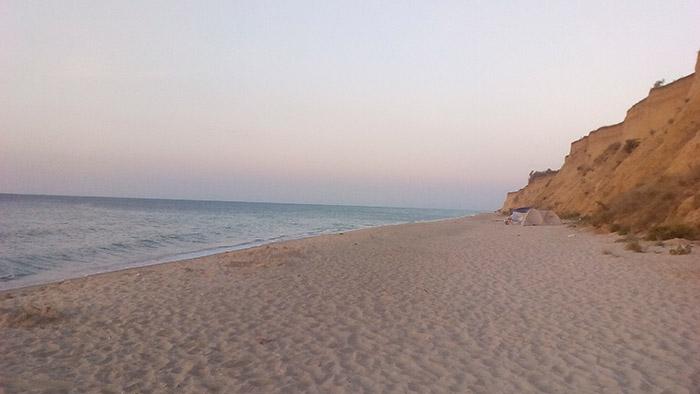 Пустий пляж та одинока палатка на березі